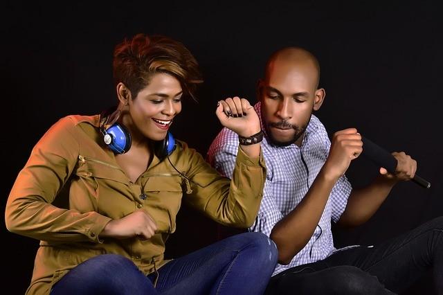 Un homme et une femme assis qui bougent leurs bras en dansant