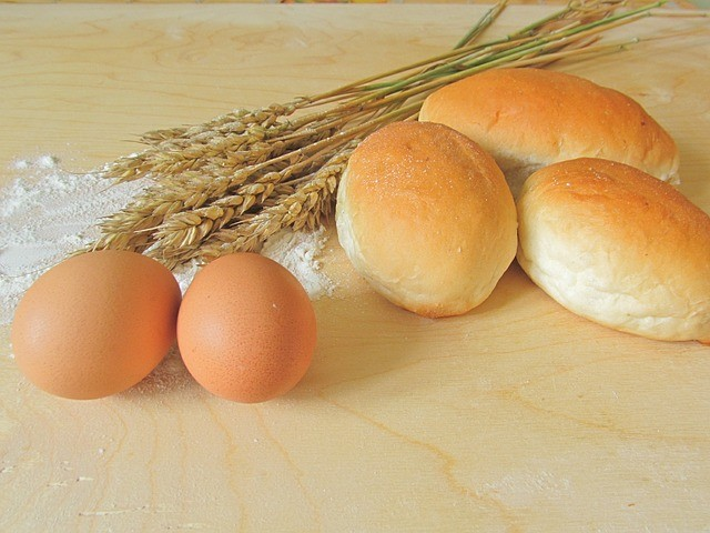 Petits pains, oeufs, farine et épis de blé