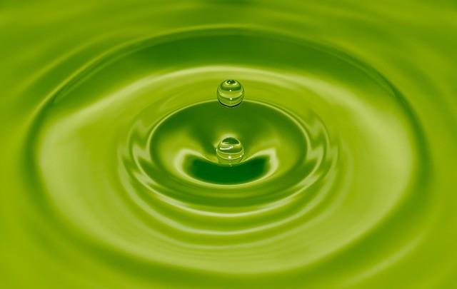 goutte d'eau tombée dans l'eau vue à travers d'un filtre optique vert
