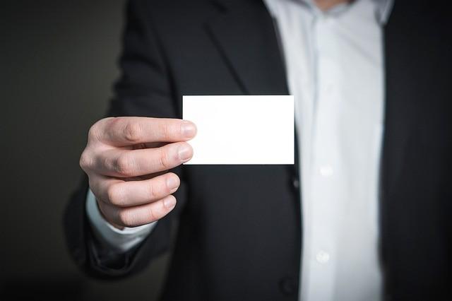 main d'un homme qui tient une carte de visite