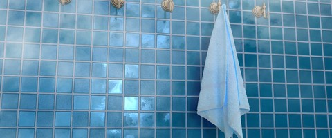 Une serviette éponge sur l'un des nombreux crochet d'un mur carrelet de petits carreaux