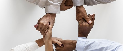 Les mains serrées ensemble de quatre personnes
