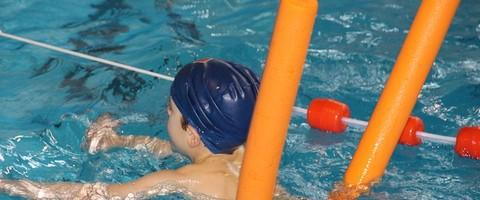 Enfant se déplaçant avec un boudin de piscine près d'une ligne d'eau